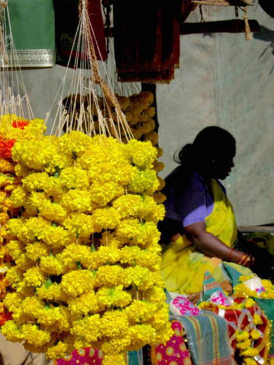 Carefully lace flowers together to sell as offerings at temple, Pune, India